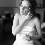 le photgraphe saisie la mariée en train d'ajuster sa boucle d'oreille