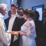 le photographe profite d'une magnifique lumière sur le prêtre et les mariés