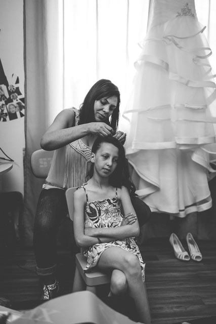 la fille de la mariée se fait coiffée devant la robe