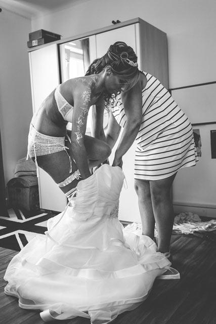 la mariée en porte jartelles entre dans sa robe sous le regard du photographe