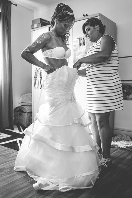 la mariée passe sa robe aidée par sa témoin