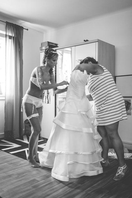 la mariée se prépare à enfiler sa robe