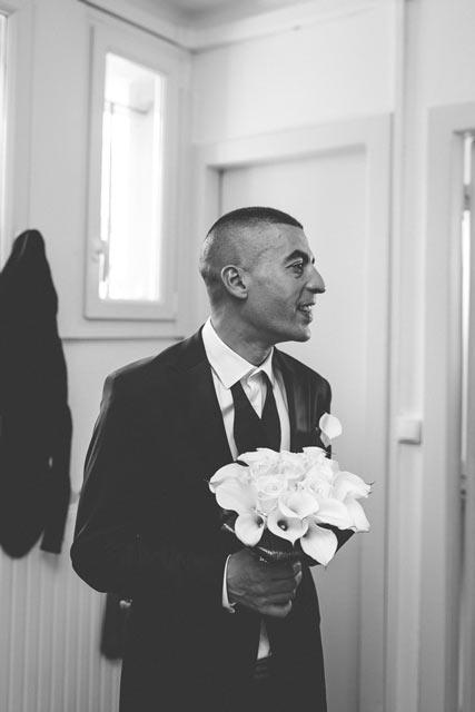 le marié attend sa future femme avec un bouquet à la main