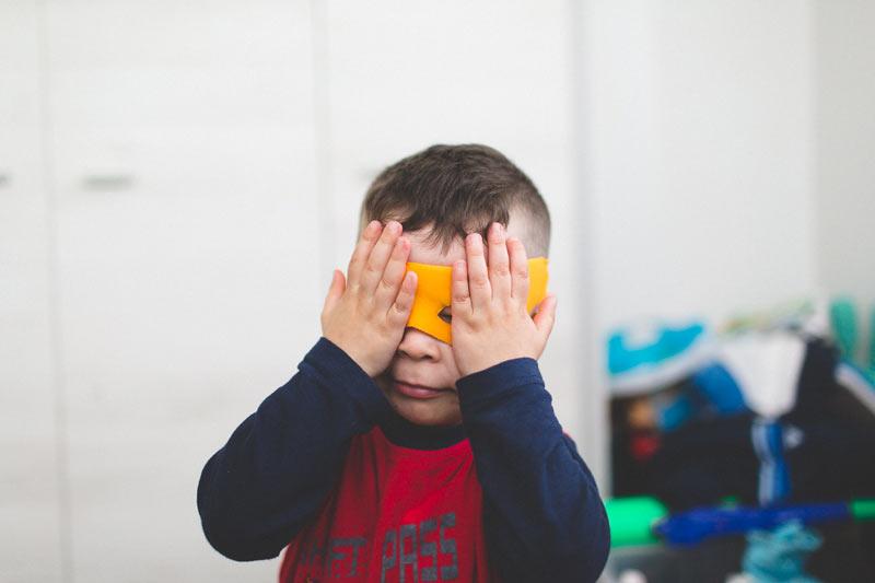 le petit garçon joue au super héro avec le photographe