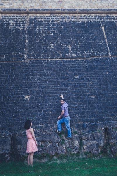 un homme grimpant au mur devant sa fiancée lors d'une séance photos de fiançailles