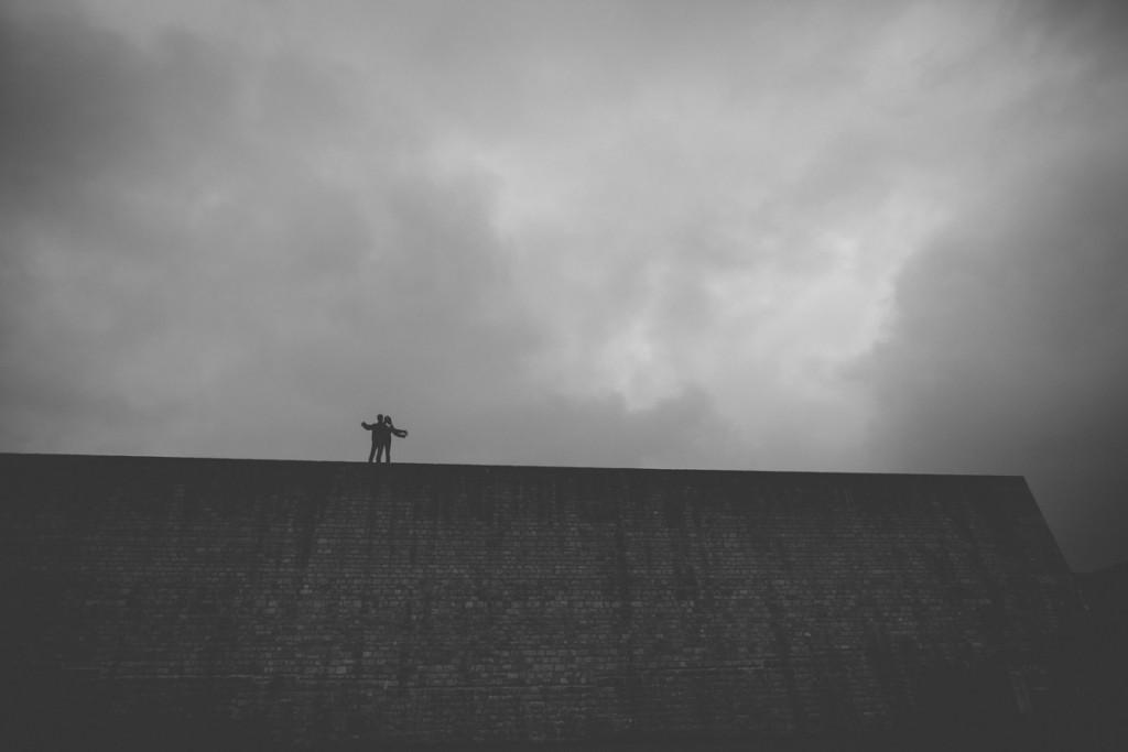 le photographe fait monter le couple en haut du mur sous un ciel orageux