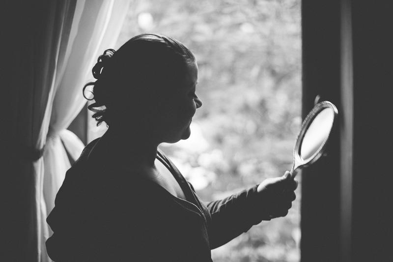 la mariée se regarde dans le miroir près de la fenêtre