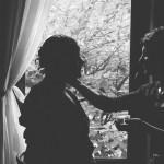 le photographe réalise une silhouette de la mariée se faisant maquiller