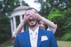 La mariée cache les yeux du marié avec ses mains