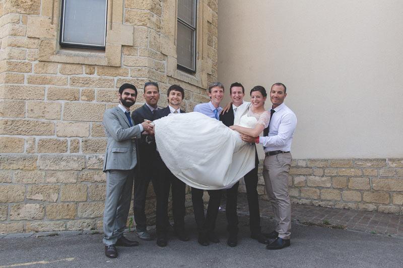 la mariée est portée par des hommes sous le regard du photographe