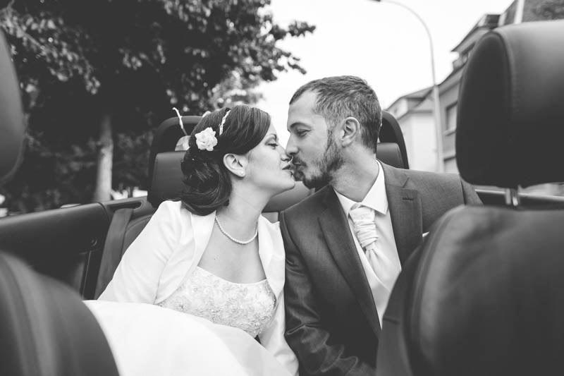 le photographe monte dans la voiture avec les mariés