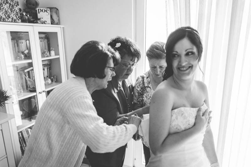le photographe profite de l'instant ou les femmes habillent la mariée