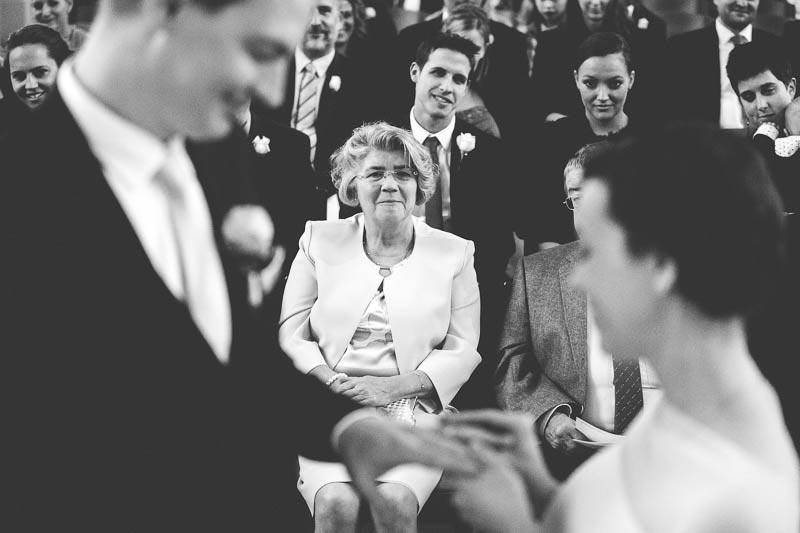 mom breaking in tears while bride puts wedding ring on groom's finger