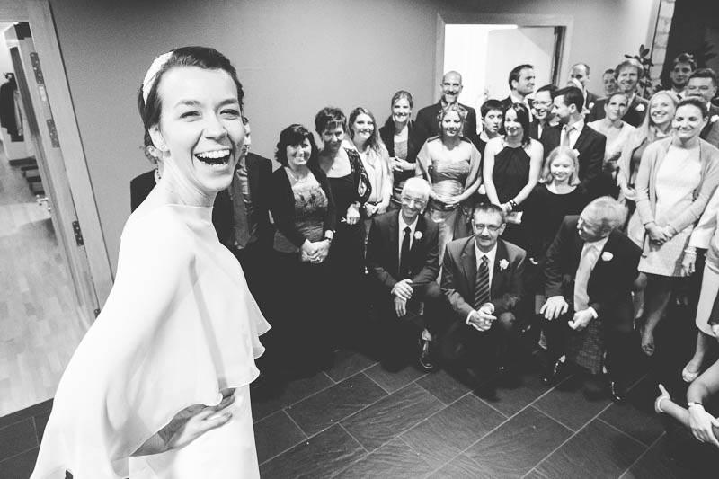 la mariée regarde le photographe en rigolant lors des photos de groupe