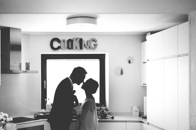 le photographe realise une silhouette des maries dans leur cuisine