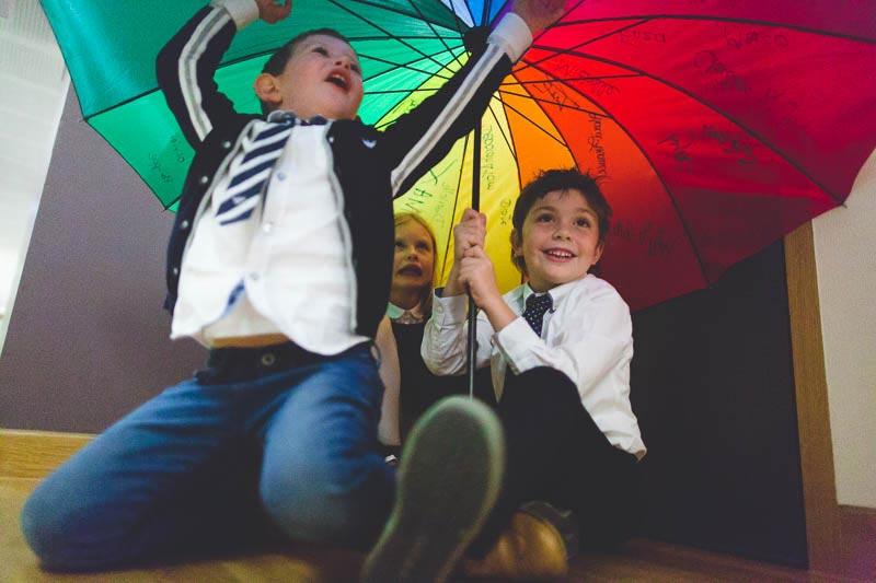 le photographe se glisse sous le parapluie avec les enfants
