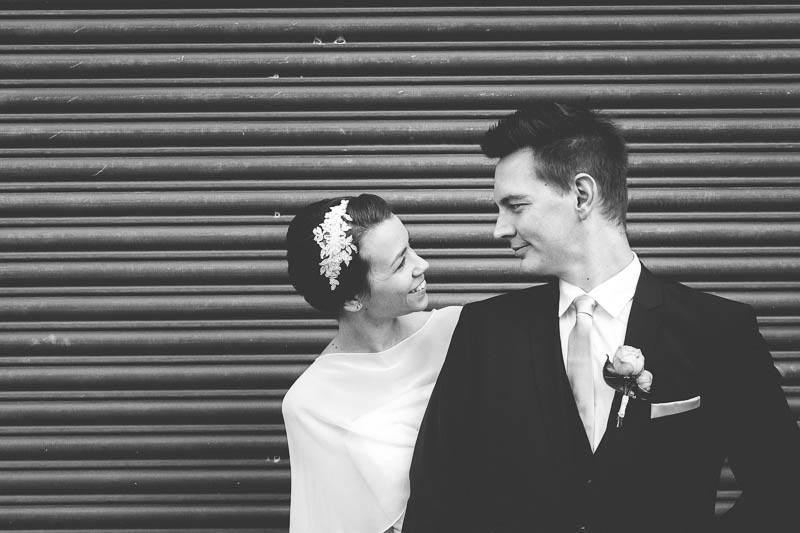 les mariés en noir et blanc devant un rideau de fer