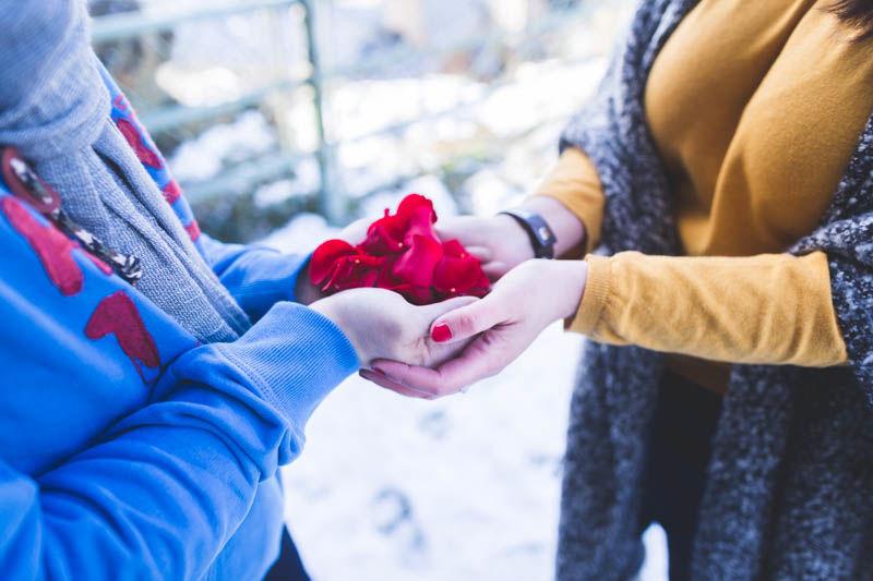 les futurs mariés tiennent des pétales de rose dans leurs mains