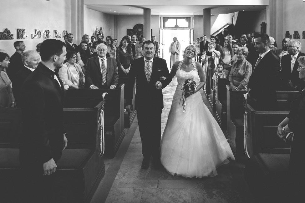 la mariée au bras de son papa marche dans l'allée de l'église d'alzingen