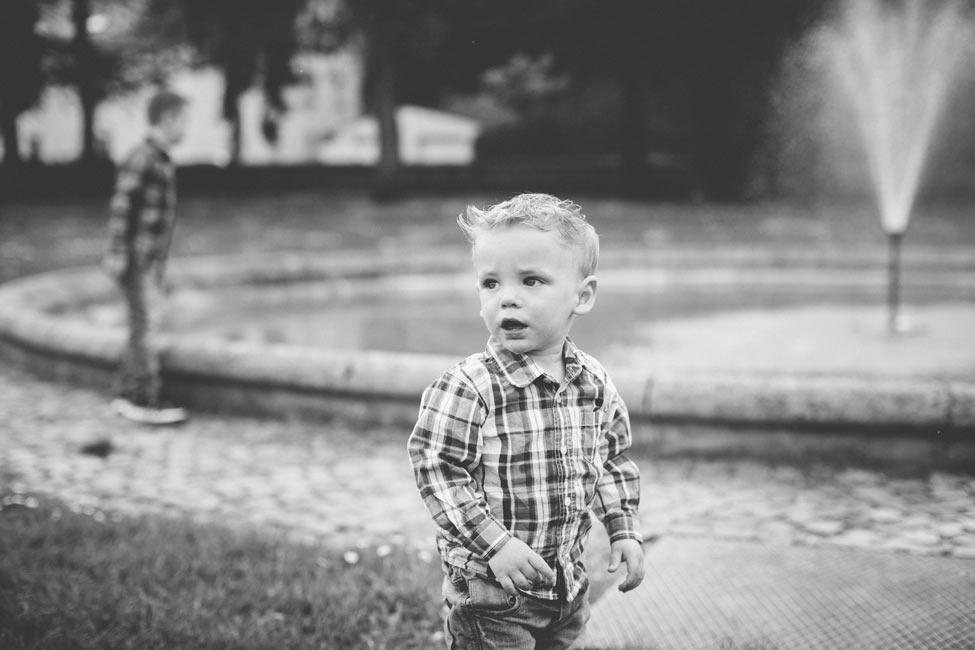 un petit garçon devant une fontaine