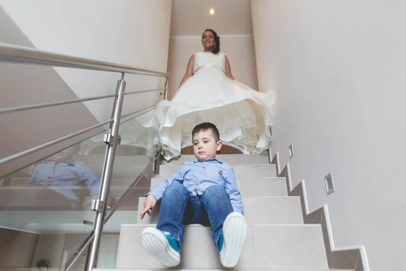 la mariée descend les escalier en recouvrant son fils avec sa robe