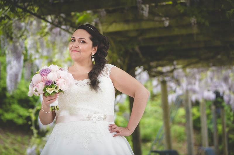 la mariée pose avec son bouqet sous un joli porche