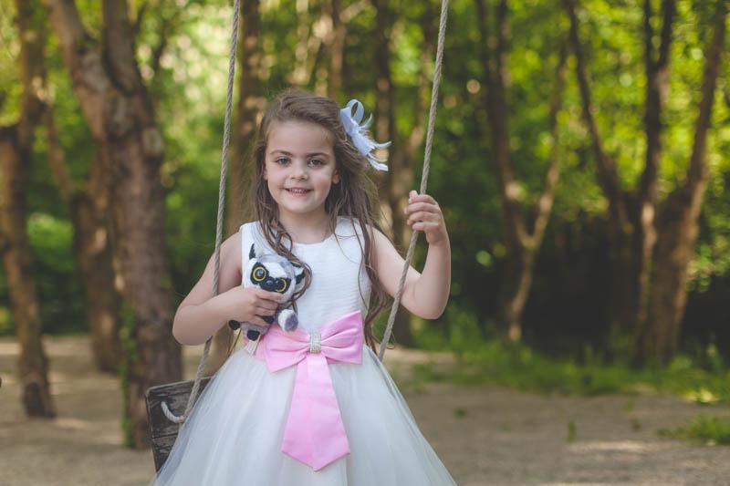 petite fille portant une robe à ruban rose joue à la balançoire