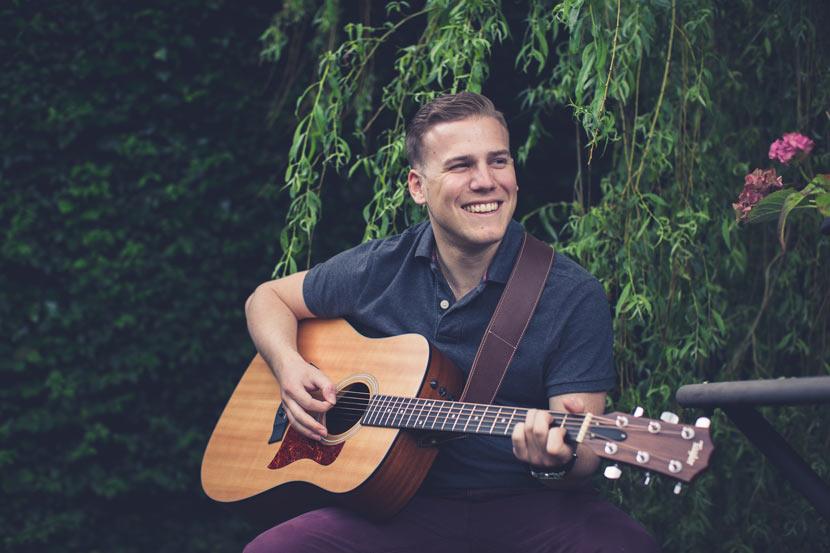 le fiancé joue de la guitare en souriant