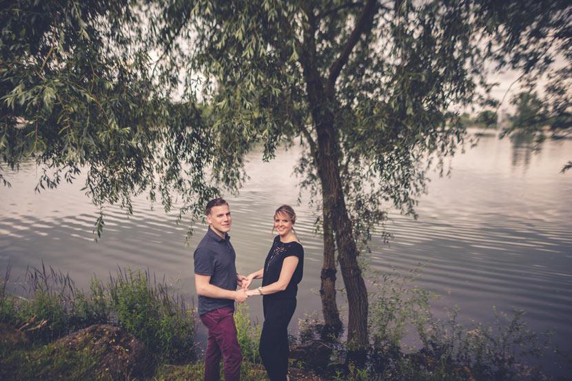 les futurs mariés se tiennent par les mains devant un lac