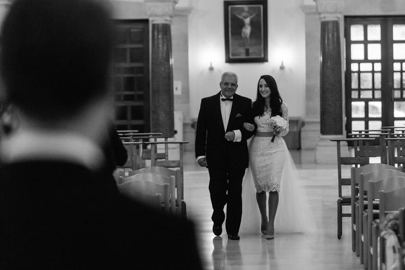 la mariée marche au bras de son père dans l'église de limpersberg