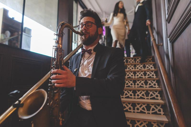 les mariés conduits à leur table par le saxophoniste