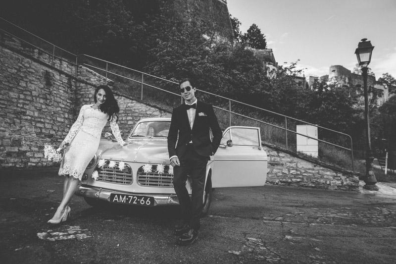 les mariés posent devant leur voiture devant les casemates du luxembourg