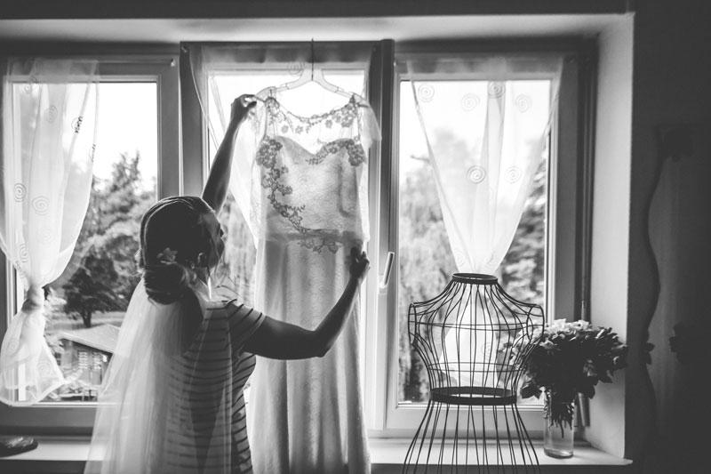 a mariée suspend sa robe à la fenetre de sa chambre