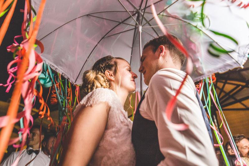 les mariés sous un parapluie de serpentins