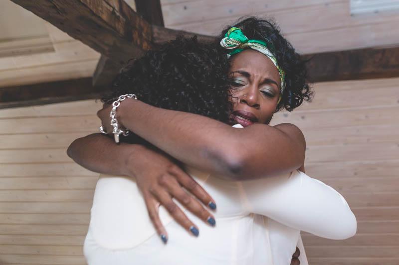 06 émotion de la mariée noire pendant qu'elle enfile sa robe