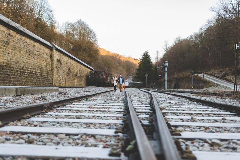 un couple marche sur les rails d'une voie ferrée