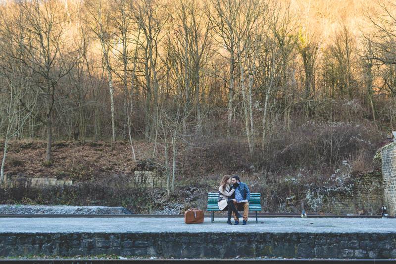 couple sur un banc attendant son train au coucher de soleil