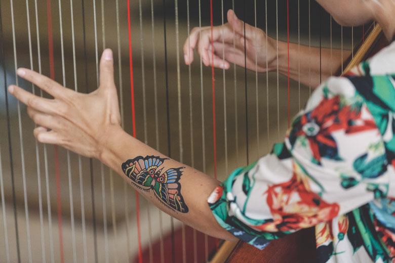 tatooed girl playing the harp