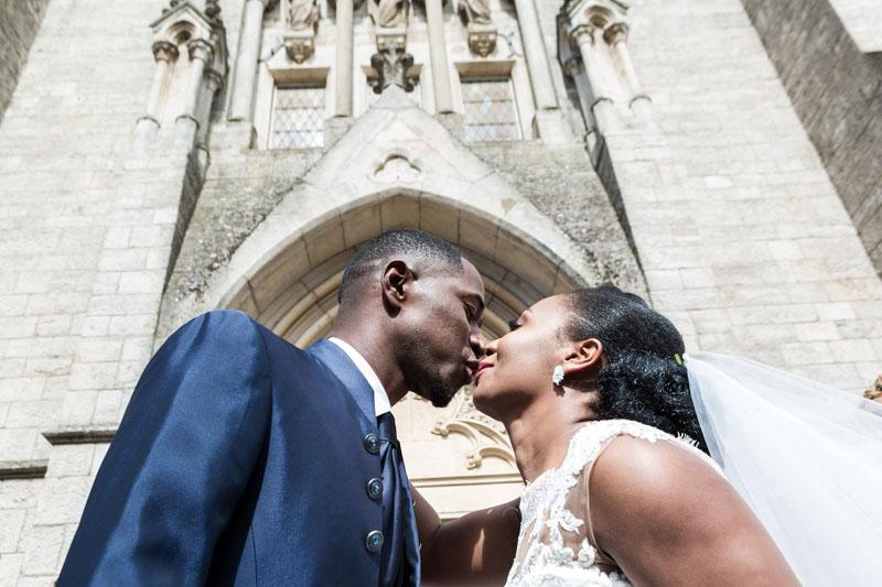 les mariés s'embrassent à la sortie de l'église