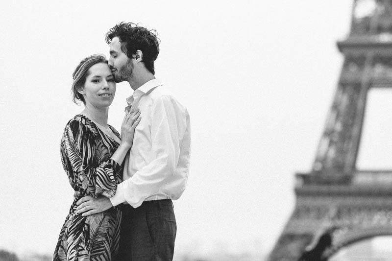 un jeune homme embrasse tendrement sa femme devant la tour Eiffel