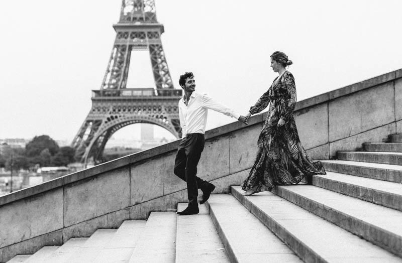 couple qui descend les marches devant la tour eiffel