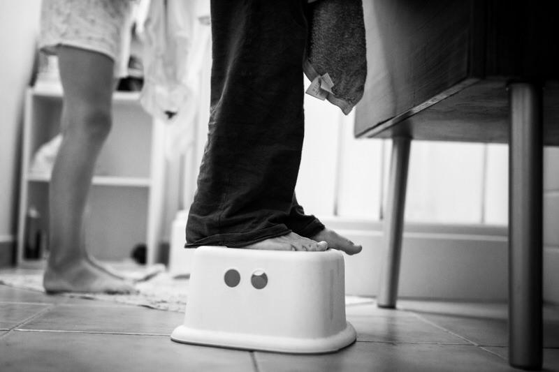 petit garcon monte sur un bac dans la salle de bain