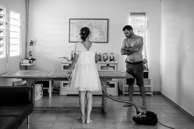 la mariée passe l'aspirateur sous le regard du marié