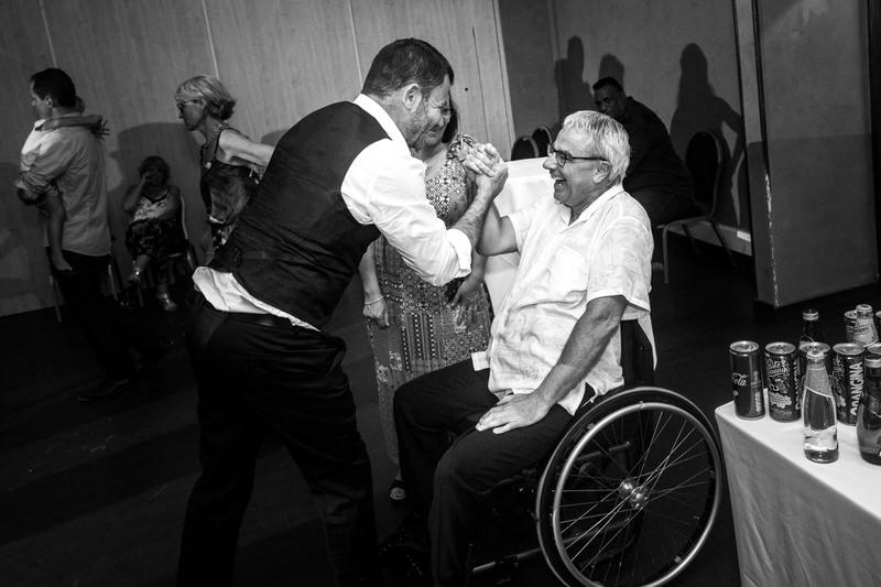 le marié tape dans la main d'un homme en chaise roulante