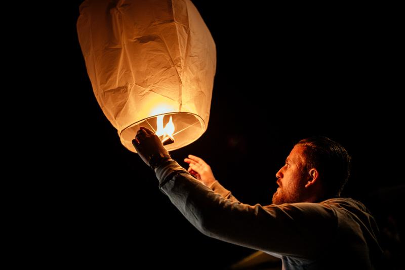 un homme allume une lanterne lors d'un mariage