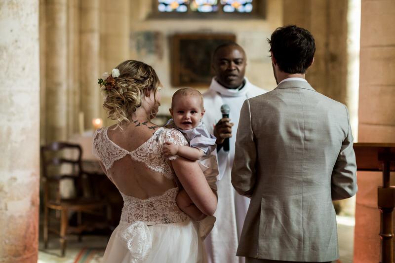 petit bébé dans les bras de la mariée qui sourit au photographe