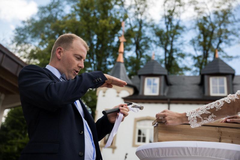 le marié ajuste le clou avant de l'enfoncer