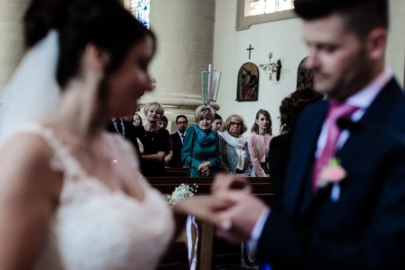 les mariés se passent la bague au doigt sous le regard de leurs parents