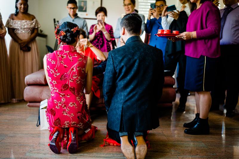 bride and groom kneeling down before their parents